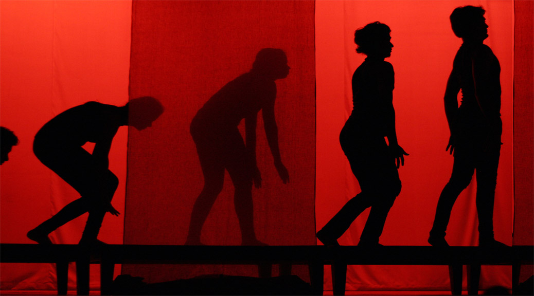 expressive human shadows on red lit stage